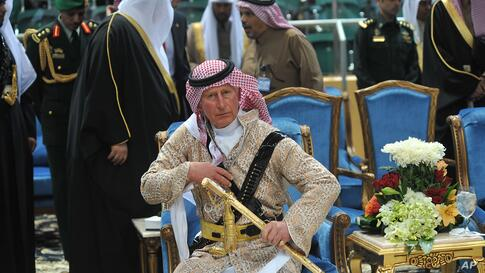 Britain's Prince Charles wears a traditional Saudi outfit as he attends the traditional Saudi dancing best known as 'Arda', performed during Janadriya culture festival at Der'iya in Riyadh, Feb. 18, 2014.