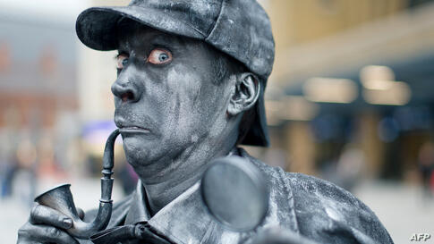 A performer poses as a Sherlock Holmes human statue at King's Cross Square, the new public area outside the central London rail station.