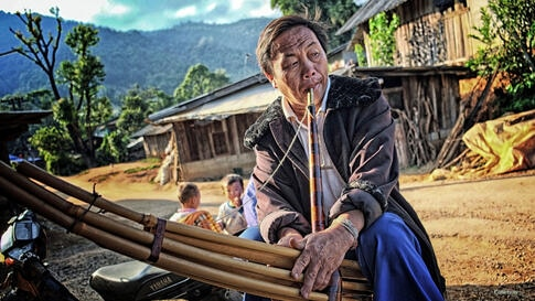 A Thai hill tribe elder plays a traditional bamboo wind instrument as the sun sets in the village of Khun Klang, Chiang Mai province, Thailand. (Photo taken by Matthew Richards/Thailand/VOA reader)