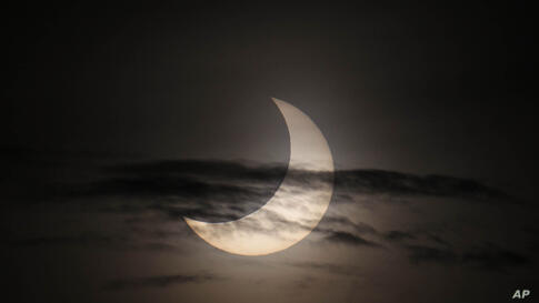 An annular solar eclipse is partially seen at sunrise, May 21, 2012, from the coastal township of Gumaca, Quezon province, southeast of Manila, Philippines.