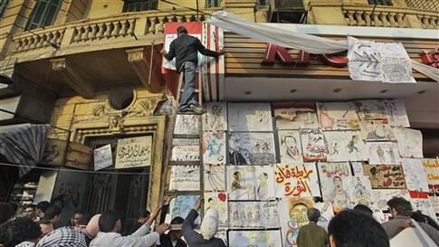 An artists hangs another political drawing on the shop front of a closed fast food outlet, in a street which has become a meeting point and workshop for artists to create such posters, at the continuing anti-government demonstration in Tahrir Square in do