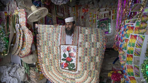 Pakistani shopkeeper Talib Hussain displays a giant sized money garland to customers in Bannu, June 18, 2014. These traditional garlands are made of local currency notes and are gifted to grooms by their friends and relatives in marriages. The garlands...