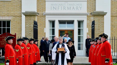 Reverend Richard Whittington carries an oak casket with the ashes of late British former Prime Minister Margaret Thatcher, ahead of her son Mark (L) and his wife Sarah (R) past an honor guard of Chelsea Pensioners after leaving the chapel at the Roya H...