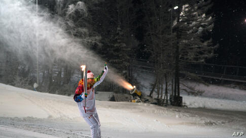 Photo released by the Sochi 2014 Winter Olympics Organizing Committee shows a torchbearer skiing at a ski resort near the Siberian city of Krasnoya, some 3500 km (2174 miles) east of Moscow, Russia.