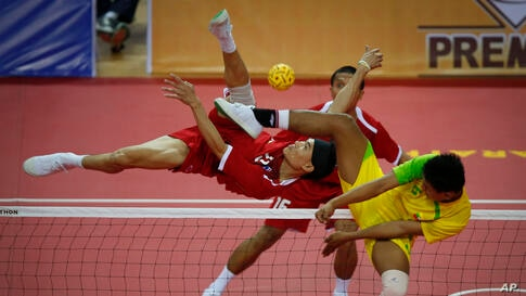 Thailand's Supachai Maneenat, left, returns a shot from Myanmar's Aung Pyah Tun, right, during their men's sepaktakraw match at the Southeast Asian (SEA) Games in Naypyitaw, Burma.