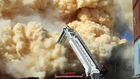 Firefighters try to extinguish a fire at a fertilizer depot in Sao Francisco do Sul, Santa Catarina, Brazil. The dense smoke, produced by ammonium nitrate at the building, forced to evacuate more than 150 families.