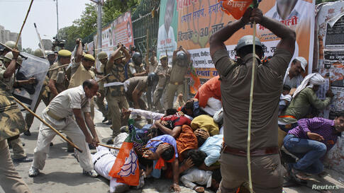 Indian policemen use batons to disperse youth wing workers of country's ruling Bharatiya Janata Party (BJP) during a protest outside the state assembly in the northern Indian city of Lucknow. Hundreds of workers protested against the state government o...