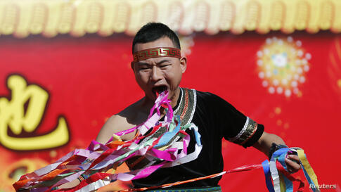 A man pulls ribbons from his mouth as he performs a feat of his strength during the opening of the temple fair for Chinese New Year celebrations at Ditan Park, also known as the Temple of Earth, in Beijing, China.