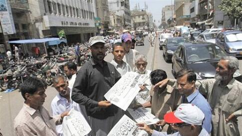 People buy newspapers reporting the killing of Al-Qaida leader Osama bin Laden in Pakistan, at local newspaper printing press in Karachi, Pakistan Monday, May 2, 2011.