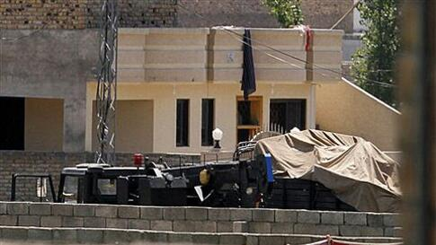 Vehicles are parked inside the compound of a house where it is  believed al-Qaida leader Osama bin Laden lived in Abbottabad, Pakistan on Monday, May 2, 2011. Bin Laden, the glowering mastermind behind the Sept. 11, 2001, terror attacks that killed thousa