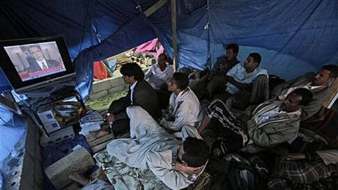 Anti-government protestors watch a TV broadcasting President Barack Obama statement on the death of Al-Qaida leader Osama bin Laden, in a tent at the site of a demonstration demanding the resignation of Yemeni President Ali Abdullah Saleh, in Sanaa,Yemen,