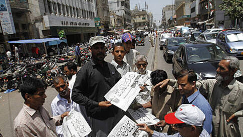 People in Karachi, Pakistan, buy newspapers reporting the killing of Osama bin Laden, May 2, 2011