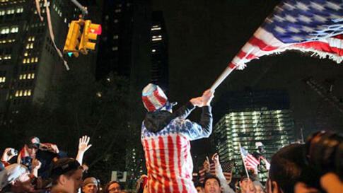 Perched on another's shoulders, Ryan Burtchell, of the Brooklyn borough of New York, center, waves an American flag over the crowd as they respond to the news of Osama Bin Laden's death, May 2, 2011