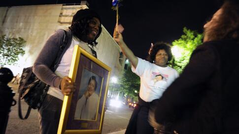 A pair of women honor their aunt, Cecelia E. Richard, who was killed in the September 11 attacks on the Pentagon, by carrying her picture amongst revelers near the White House after U.S. President Barack Obama announced that U.S. authorities have recovere