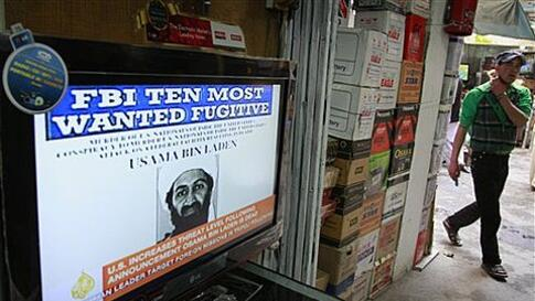An Afghan youth walks past by a television  announces the death of Al-Qaida leader Osama bin Laden at a television selling market in Kabul, Afghanistan on Monday, May 2, 2011. Bin Laden, the glowering mastermind behind the Sept. 11, 2001, terror attacks t