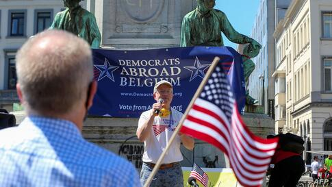A man waves a US national flag as people attend a gathering of Democrats Abroad Belgium (DAB) to welcome the visit of US…