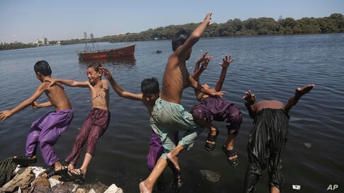 Kids jump into water to cool themselves off as the temperature soars in Karachi, Pakistan, Wednesday, June 24, 2020. Many…