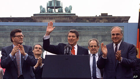 ** FILE ** In this June 12, 1987 file photo U.S. President Reagan acknowledges the crowd after his speech in front of the…