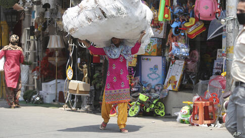 A laborer carries a load of plastic toys at a market in Jammu, India, Friday, June 19, 2020. India is the fourth hardest-hit…