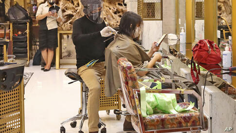 An employee wearing protective gear gives a haircut at a beauty salon in the Senayan City shopping mall during its first day of…