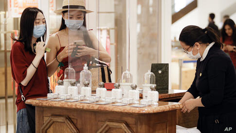 Sales assistants and customers wear protective equipment at the Selfridges department store in London, Monday, June 15, 2020…