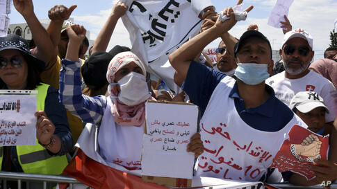 """Tunisian Graduates unemployed hold a placards that reads """"I spend all my life to build and reform, but you make me lost my life…"""
