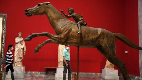 A couple wearing face masks to prevent the spread of the new coronavirus, look at the 140 B.C. bronze statue of a young jockey…