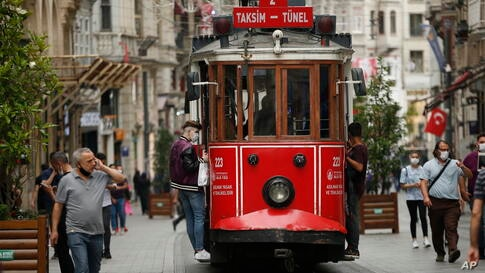 People, wearing protective masks against the spread of coronavirus, walk and use the tram on Istiklal street, the main shopping…