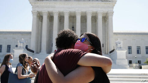 Anti-abortion protesters hug goodbye outside the Supreme Court on Capitol Hill in Washington, Monday, June 29, 2020.  The…