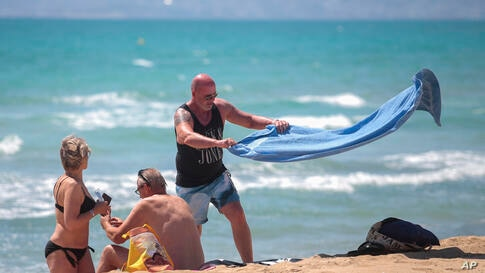 German tourists arrive at the beach of Palma de Mallorca, Spain, Monday, June 15, 2020. Borders opened up across Europe on…