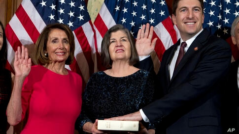 House Speaker Nancy Pelosi of Calif., administers the House oath of office to Rep. Bryan Steil, R-Wis., during ceremonial…