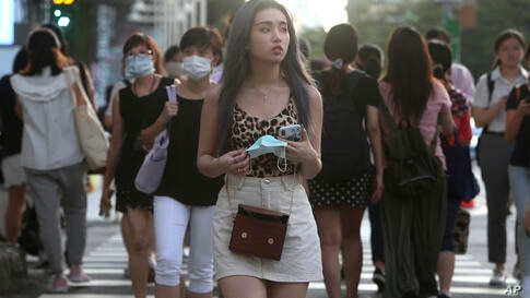 People walking thorough the streets of downtown Taipei, Taiwan, with face masks to help curb the spread of the coronavirus,…