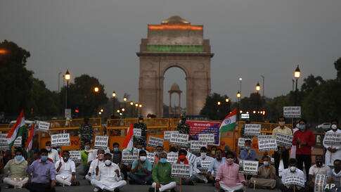 Members of ruling Bharatiya Janata Party sit in front of India Gate monument in New Delhi, India, holding candles as tributes…