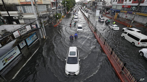 Motorists navigate along a flooded street during a brief downpour on Monday, June 15, 2020 in Manila, Philippines. (AP Photo…