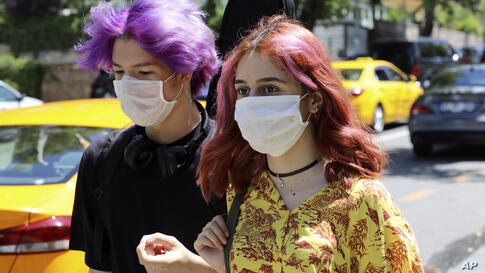 Young people wearing face masks to protect against the spread of coronavirus, walk in Ankara, Turkey, Friday, June 26, 2020…