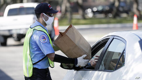 A member of Orange County Fire Rescue passes out personal protective equipment (PPE) items including disposable face masks,…