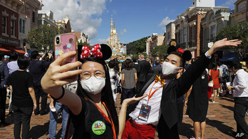 Visitors wearing face masks to prevent the spread of the new coronavirus, take a selfie at the Hong Kong Disneyland on Thursday…