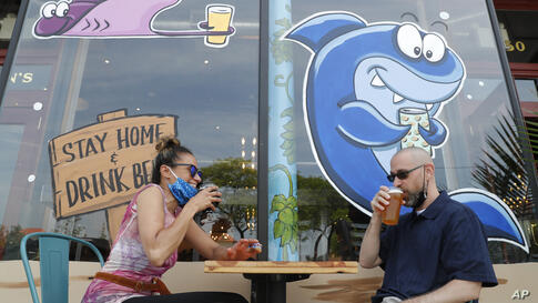 Jennifer Udvadia, left, and Patrick Bounaiux share drinks at Bright Eye Beer Company Wednesday, June 10, 2020, in Long Beach, N…