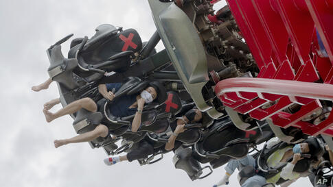 """Visitors wear their face masks to help curb the spread of the coronavirus, as they ride the """"Vortex"""" rollercoaster at the…"""