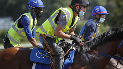 Riders wearing masks workout horses at Belmont Park in Elmont, N.Y., Wednesday, June 17, 2020. The 152nd running of the Belmont…