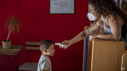 Hugo, 3, has his temperature taken by a teacher as he arrives at Cobi kindergarten in Barcelona, Spain, Friday, June 26, 2020…