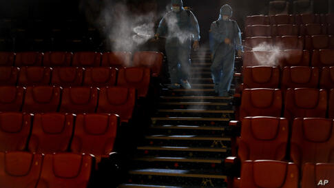 Staff of a cinema spray disinfectant at the cinema hall to prepare for reopening on July 1 in Kuala Lumpur, Malaysia, Friday,…