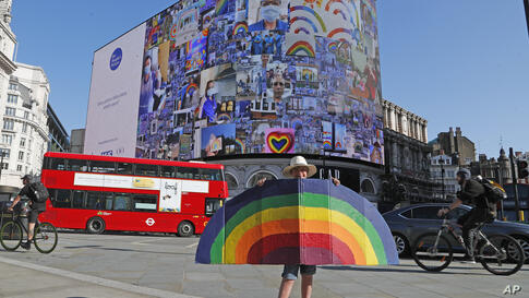 A young boy holds a painted rainbow as pictures appear on a screen during a 10 minute domination on The Piccadilly Lights,…