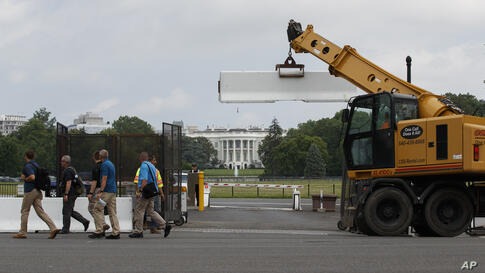 Concrete barricades that secure the interior base of the temporary perimeter fence surrounding the White House area are removed…