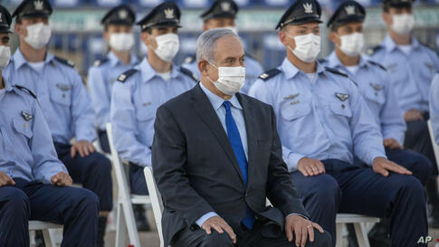Israeli Prime Minister Benjamin Netanyahu wearing a face mask attends a graduation ceremony for new pilots in Hatzerim air…