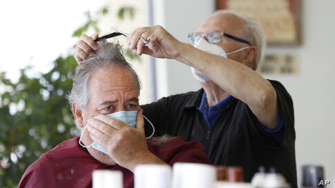 Barber Nicola Oricchio, right, cuts Jerry Swanson's hair, Wednesday, June 10, 2020, at Majestic Barber Shop in Long Beach, N.Y…