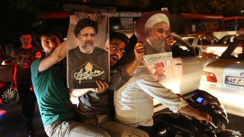 A supporter of Iranian President Hassan Rouhani, right, holds his poster as the other one holds a poster of his main rival…