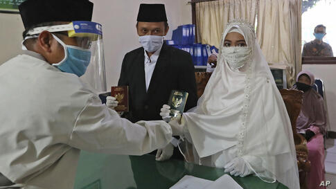 Bride Karlina and groom Cahya Sudrajat receive their marriage certificate from Muslim officiant Solehchudin while all wear…