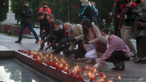 People lay flowers and light candles at the Tomb of Unknown Soldier in Moscow, Russia, early Monday, June 22, 2020, marking the…