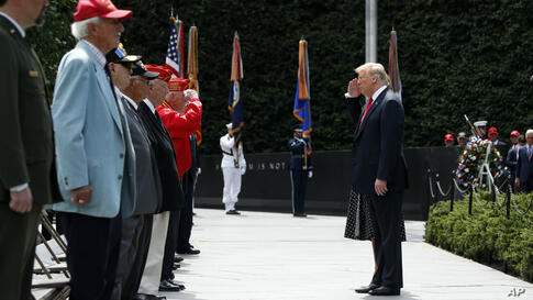 President Donald Trump salutes as he speaks with veterans after a wreath placing ceremony at the Korean War Veterans Memorial,…